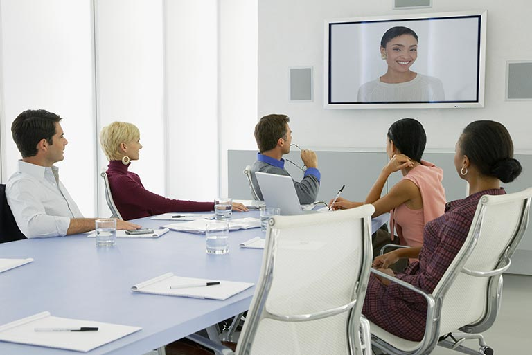 Business group watching monitor installed on wall